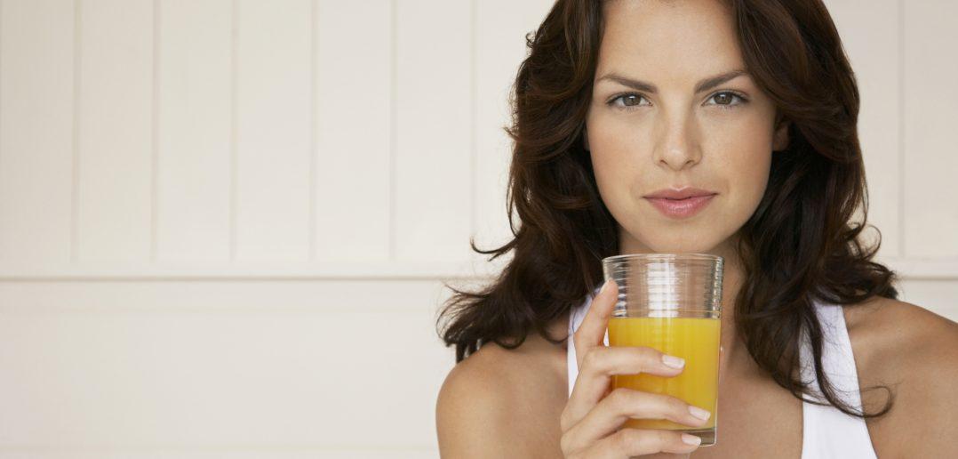 Smuk kvinde drikker juice